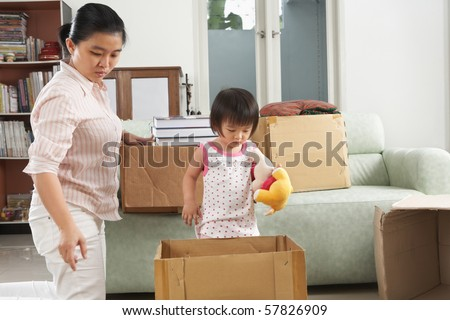 Mother and daugher packing items for moving house