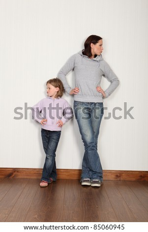 Mother and daughter after dispute, looking away with angry face and sulking from family argument. Both wearing denim jeans and hoodie.