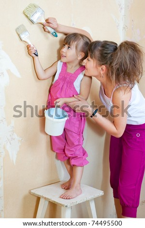 Mother and daughter are doing repairs together, primed the wall under the wallpaper