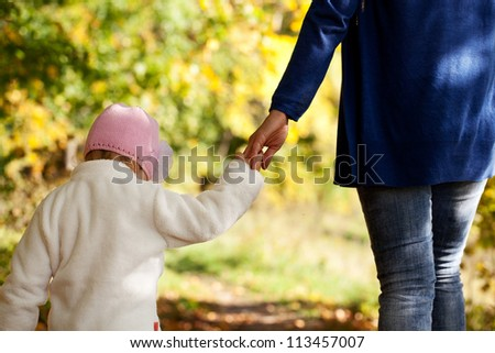 Mother and daughter are holding hands in the autumn forest