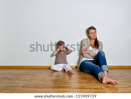 Mother and daughter are in quarrel, sitting on the floor and looking sideway