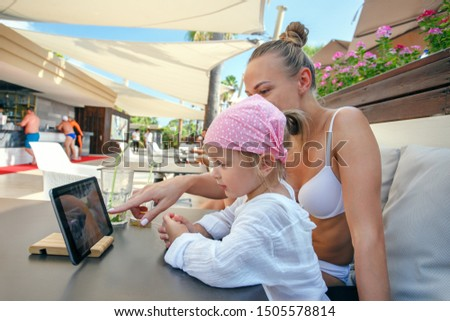 Mother and daughter at beach cafe and looking at the digital tablet screen. Foto stock ©
