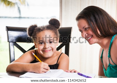 Mother and daughter at home. Mom teachs little girl homework.
