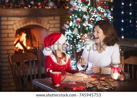 Mother and daughter baking Christmas cookies at fire place and decorated tree. Mom and child bake Xmas sweets. Family with kids celebrating Christmas at home. Little girl cooking in the kitchen. #745945753