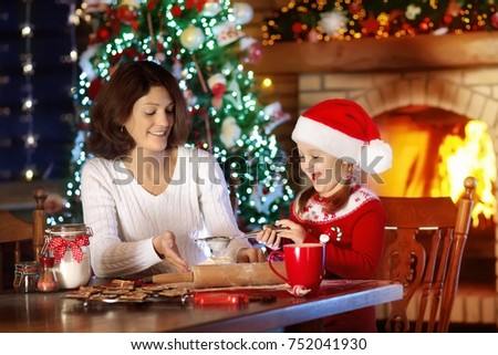 Mother and daughter baking Christmas cookies at fire place and decorated tree. Mom and child bake Xmas sweets. Family with kids celebrating Christmas at home. Little girl cooking in the kitchen.