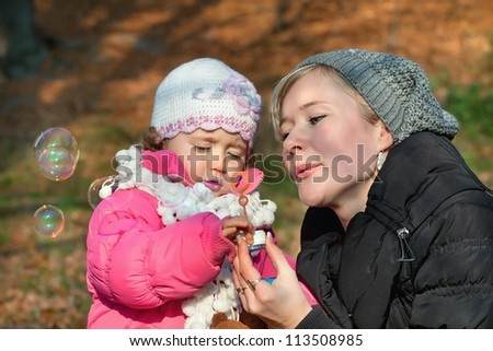 Mother and daughter blowing bubbles in the park