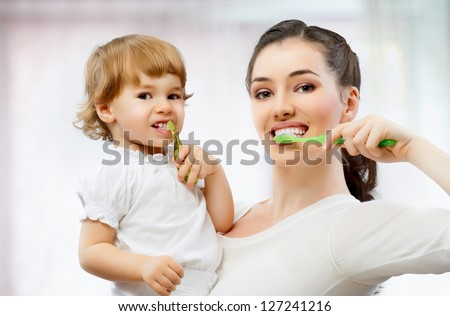 mother and daughter brush their teeth