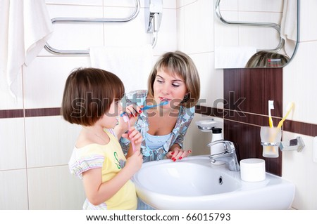 Mother and daughter brushing their teeth in bathroom