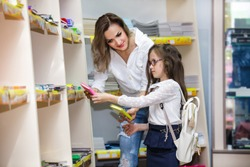 Mother and daughter buying school notebook and stationery in mall. Schoolgirl with glasses and backpack in a supermarket.