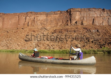 Mother and daughter canoeing on a calm blue river in the desert country of Utah