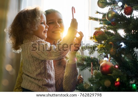 Mother and daughter celebrate Christmas in a decorated house with a Christmas tree #762829798