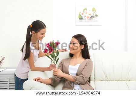 Mother and daughter. Cheerful daughter presenting flowers to mother