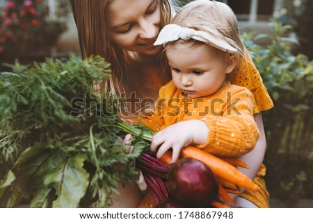 Mother and daughter child with organic vegetables healthy eating lifestyle vegan food homegrown beet and carrot local farming grocery shopping agriculture concept