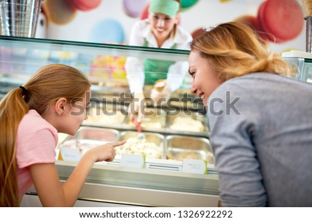 Mother and daughter chooses ice cream in colorful confectionery shop