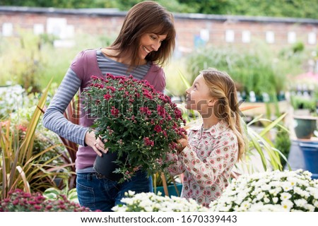 Mother and daughter choosing plants in garden center store holding potted plant