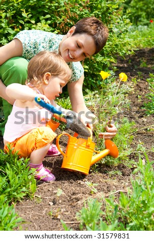 Mother and daughter cultivating the garden