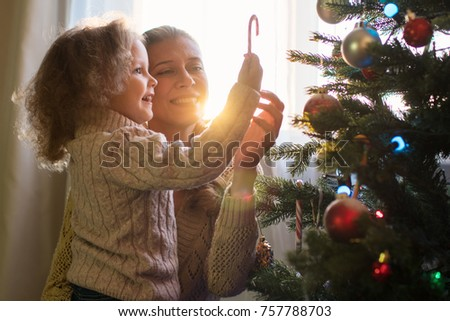 Mother and daughter decorate a Christmas tree against the window with a setting sun and bright sunlight #757788703