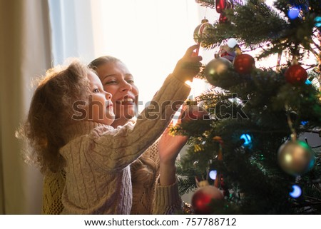 Mother and daughter decorate a Christmas tree against the window with a setting sun and bright sunlight #757788712