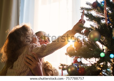 Mother and daughter decorate a Christmas tree against the window with a setting sun and bright sunlight #757788757
