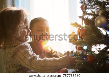 Mother and daughter decorate a Christmas tree against the window with a setting sun and bright sunlight #757788760