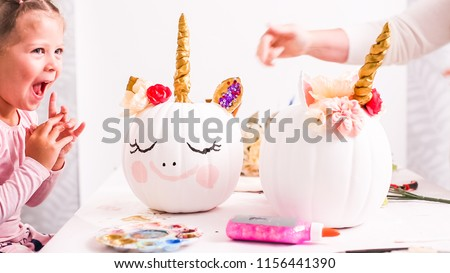 Mother and daughter decorating craft pumpkins with unicorn theme for Halloween.