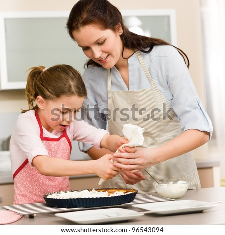 Mother and daughter decorating pie with whipped cream