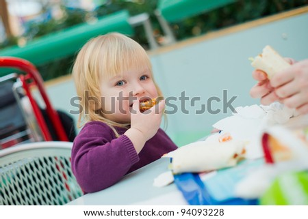 Mother and daughter dinning fast food meal in mall