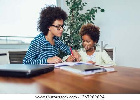 Mother and daughter doing homework learning to calculate
