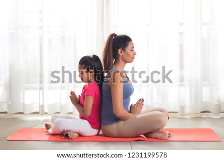 Mother and daughter doing yoga and meditating sitting back to back