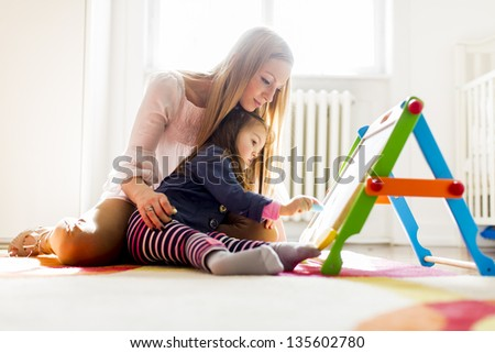 Mother and daughter drawing in the room