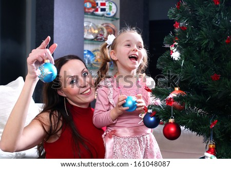 mother and daughter dress up a Christmas tree