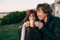 Mother and Daughter Drinking from Coffee Cups at Sunset at the Beach laughing