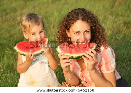 mother and daughter eat watermelon on the grass