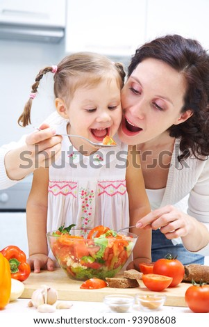Mother and daughter eating vegetables saladr in kitchen