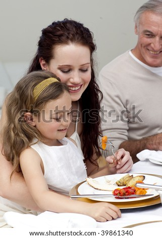 Mother and daughter eating with their family at home - stock photo