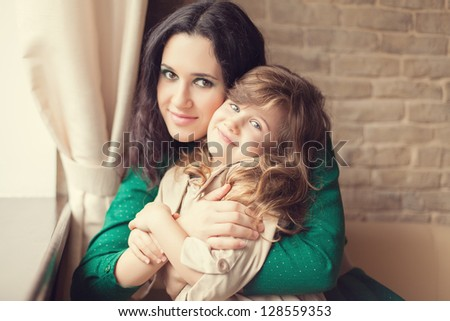 Mother and daughter embracing at home