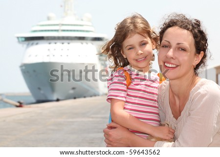 mother and daughter embracing, smiling and looking at camera, big cruise liner on background