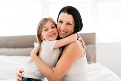 Mother and daughter enjoy in bed at home