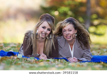 Mother and daughter enjoying a sunny autumn day in the park