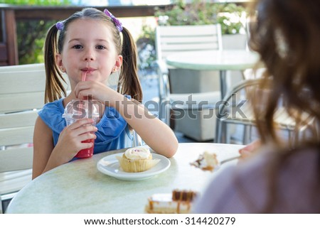 Mother and daughter enjoying cakes at cafe terrace on a sunny day #314420279