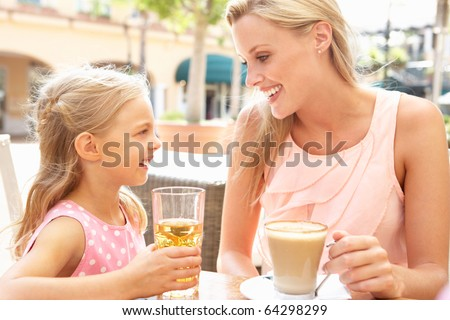 Mother And Daughter Enjoying Cup Of Coffee And Juice In Cafe Together