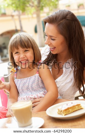 Mother And Daughter Enjoying Cup Of Coffee And Piece Of Cake In Cafe