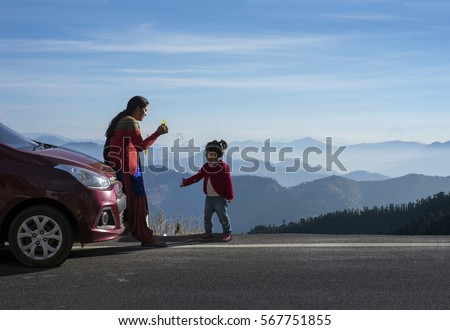 Shutterstock Mother and daughter enjoying the road trip and winter vacation. Car travel vacation concept photo against Himalayan mountain in the background.