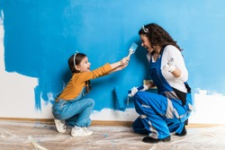 Mother and daughter enjoying together while painting wall.