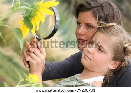 Mother and daughter examining a sunflower through a magnifying glass