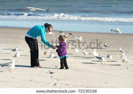 mother and daughter feeding birds at the beach