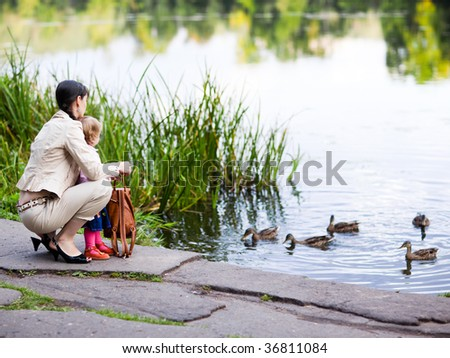 Mother and daughter feeding ducks - shallow DOF, focus on people - stock photo