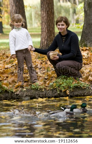 Mother and daughter feeds duck over pond