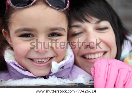 Mother and daughter giggling in the snow
