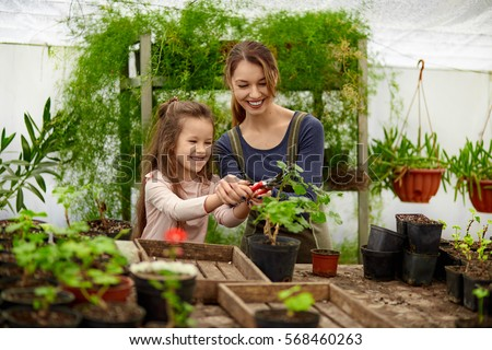 Mother And Daughter Growing Plants In Greenhouse #568460263